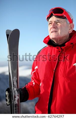 Portrait of a senior man with skis on snow - stock photo