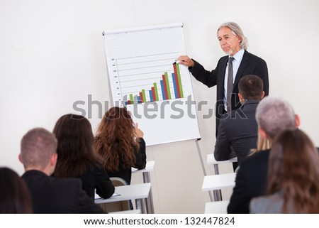 Portrait Of A Senior Manager Giving Presentation To His Colleagues At Office
