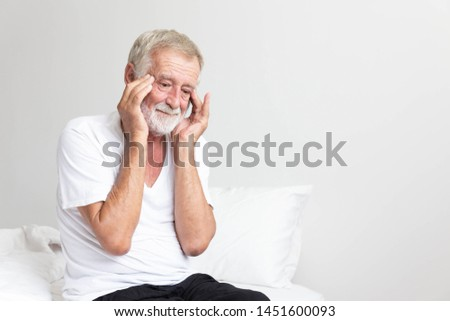 Portrait of a senior retirement man sitting and thinking alone on bed in his home #1451600093