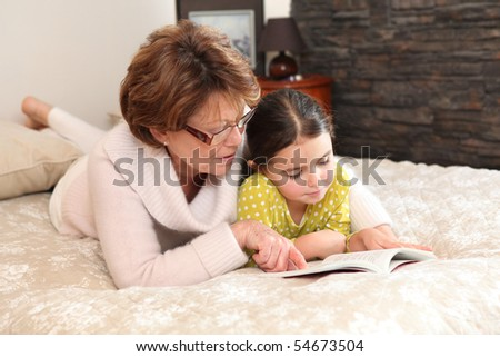 Portrait of a senior woman and a little girl stretched out on a bed reading a book