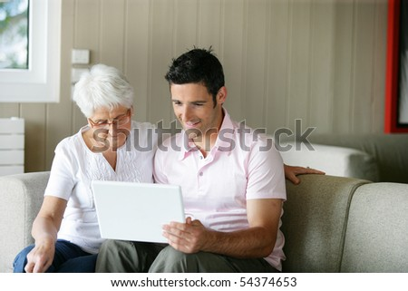 Portrait of a senior woman and a man in front of a laptop computer