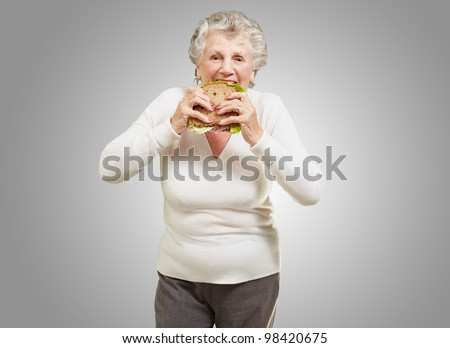 portrait of a senior woman eating a vegetable sandwich over a grey background