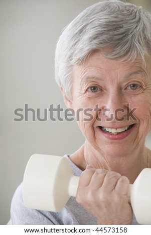 Portrait of a senior woman exercising with a hand weight