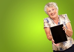 Portrait Of A Senior Woman Holding A Digital Tablet On Green Background