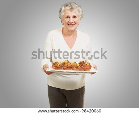 portrait of a senior woman holding a tray with muffins against a grey background