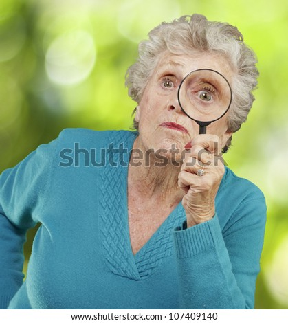 portrait of a senior woman looking through a magnifying glass against a nature background - stock photo