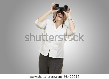 portrait of a senior woman looking through binoculars against a grey background