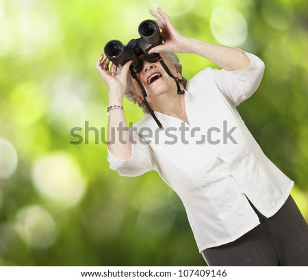 portrait of a senior woman looking through binoculars against a nature background
