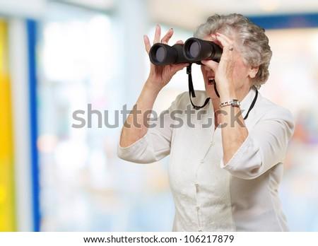portrait of a senior woman looking through binoculars indoor