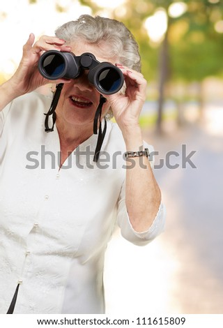 Portrait of a senior woman looking through binoculars, outdoor