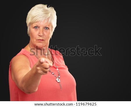 Portrait Of A Senior Woman Pointing Finger On Black Background
