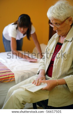 Portrait of a senior woman reading a book near a young woman making her bed