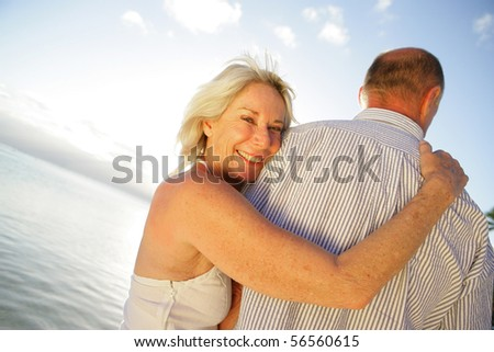 Portrait of a senior woman smiling embracing a senior man at the seaside