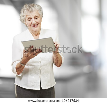 portrait of a senior woman touching a digital tablet, indoor