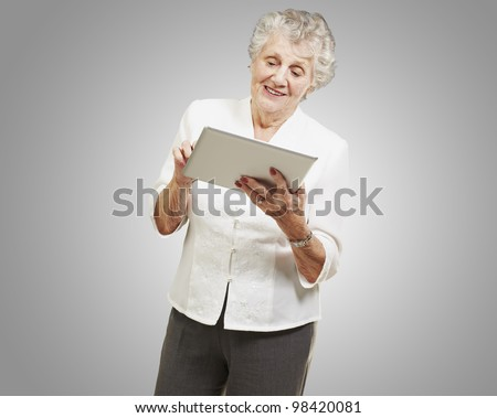 portrait of a senior woman touching a digital tablet over a grey background