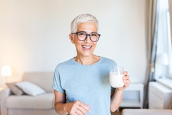 Portrait of a senior woman with a glass of milk. Beautiful elderly woman in grey T-shirt with a glass of milk. Senior woman drinking milk at home