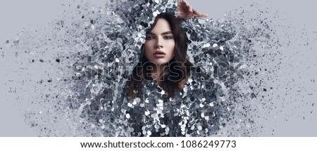 Portrait of a sensual beautiful brunette woman in a shiny fashion dress of sequins with dispersion effect on a white background in studio