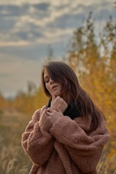 Portrait of a sensual girl in a coat in the fall forest, touching her face.