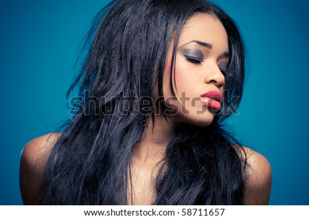Portrait of a sensual young woman, isolated on blue - stock photo