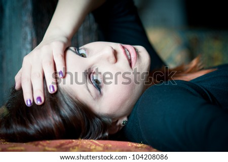 Portrait of a sensual young woman lying on sofa. Shallow depth of field. #104208086