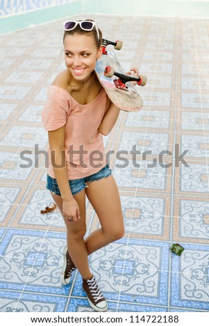 Portrait of a sensual young woman with a skateboard in her hand, outdoors