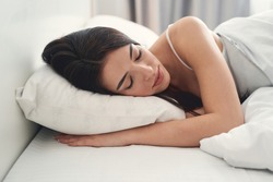 Portrait of a serene dark-haired young Caucasian woman sleeping peacefully in her bed at home