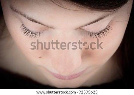 Portrait of a serene young woman, teenage girl, contemplating, looking down with her eyes closed
