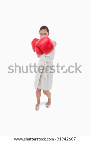 Portrait of a serious businesswoman punching someone against a white background