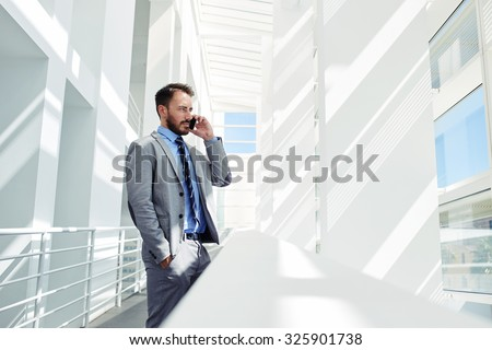 Portrait of a serious confident man boss having mobile phone conversation while resting after meeting with his partners, businessman talking on cell telephone while standing in modern space indoors