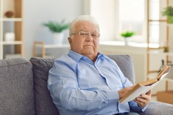 Portrait of a serious focused senior man with glasses sitting on the couch and reading an interesting book. Retired man is useful to spend his free time at home.