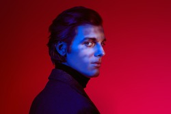 Portrait of a serious handsome man in elegant clothes  with shadows on his face in dark blue light on red  background at studio.