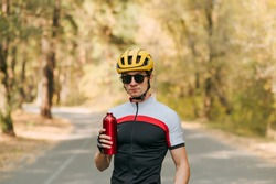 Portrait of a serious male cyclist with a bottle of water in his hand stands against the backdrop of an autumn landscape in the forest and looks int camera, wearing sports equipment and sunglasses.