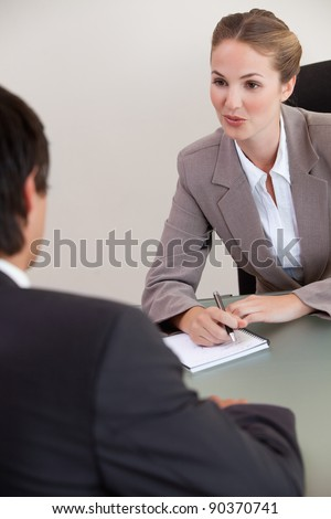 Portrait of a serious manager interviewing a male applicant in her office