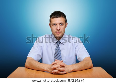 Portrait of a serious office worker man at the table on blue background
