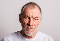 Portrait of a serious senior man in a studio, looking at camera.