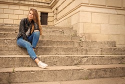 Portrait of a serious woman sitting on steps