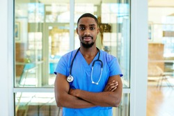 Portrait of a serious young male doctor or nurse wearing blue scrubs uniform and stethoscope, with arms crossed in hospital