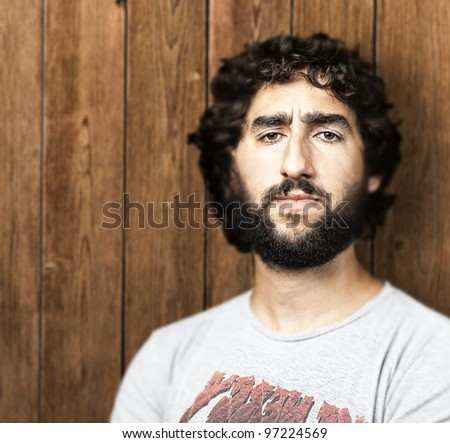 portrait of a serious young man against a wooden wall