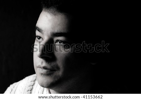 Portrait of a serious young man in dramatic lighting.