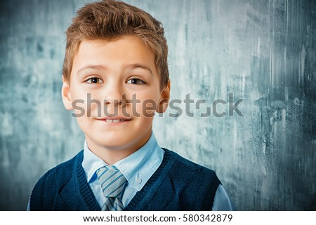 Portrait of a seven year old boy with trusting open look. Kid's fashion. Education.  #580342879