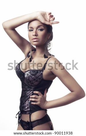 Portrait of a sexy african woman posing in lingerie on white background