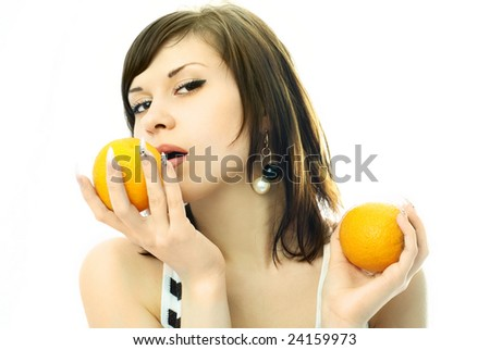 portrait of a sexy beautiful brunette woman eating oranges