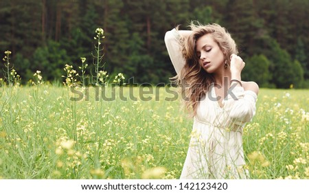 Portrait of a sexy blond girl in a field