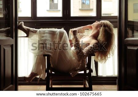 Portrait of a sexy blonde woman in window