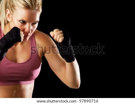 Portrait of a sexy fitness woman ready to fight. Isolated on black with copy space. - stock photo