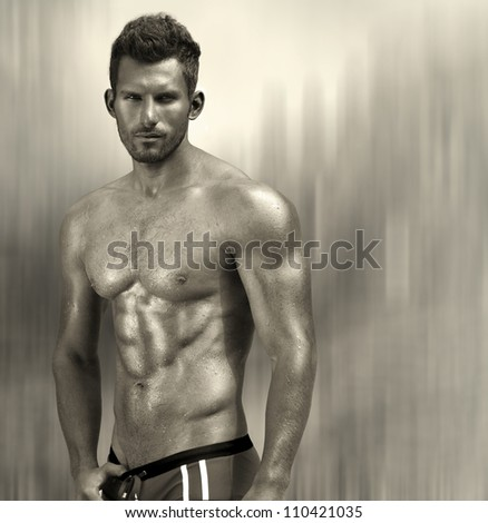 Portrait of a sexy muscular male model against modern abstract metallic background with copy space