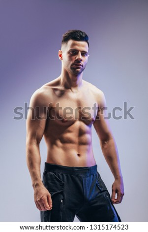 Portrait of a sexy muscular shirtless man posing in studio