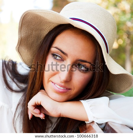 Portrait of a sexy young female smiling in a park while sitting on bench and looking away - Outdoor