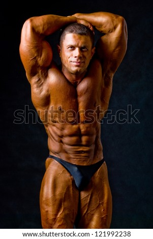 Portrait of a sexy young macho man showing his strong biceps.