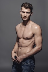 Portrait of a sexy young man with muscular body posing at studio. Gray background. Men's health.